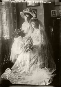 A bride and her maid of honour pose with their bouquets before the wedding in 1910.